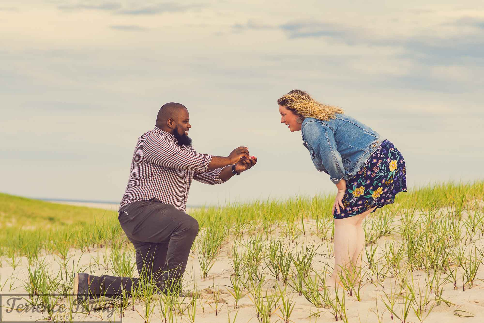 A man proposes marriage to his girlfriend on a grassy Chatham Beach as she looks down in disbelief.