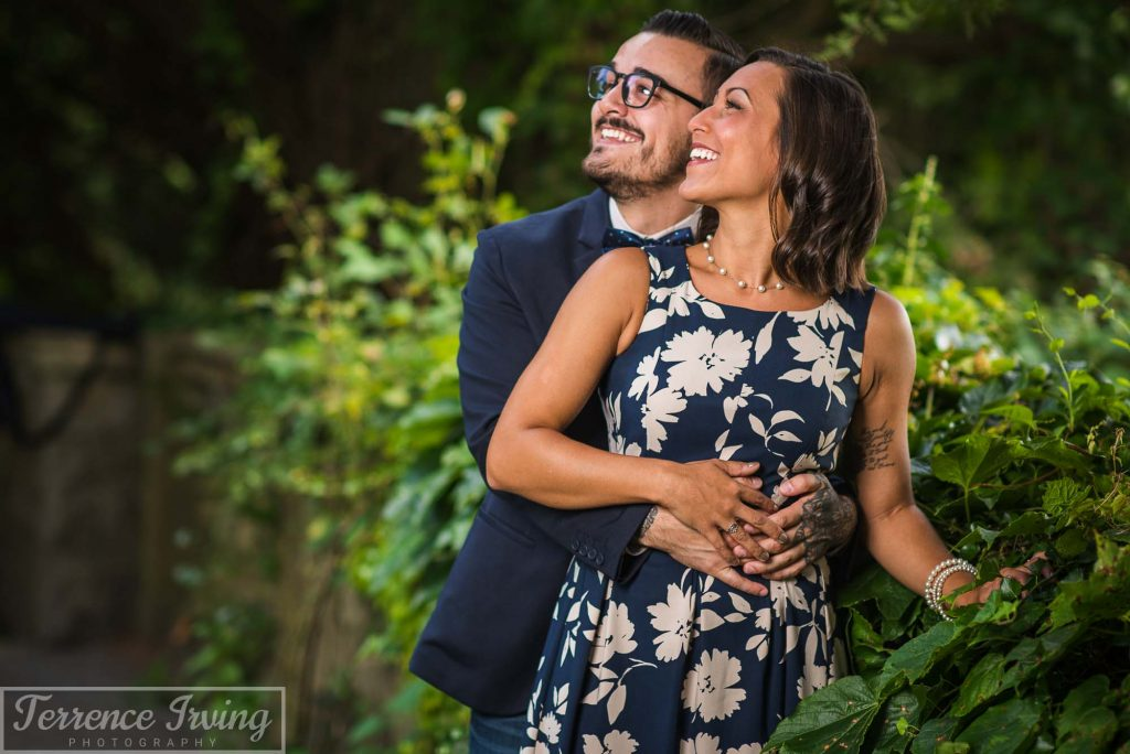 A Connecticut couple, man and woman, embrace, smile, and stand in front of a stone wall covered in green ivy.