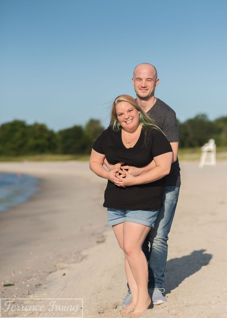 With a blue sky above them, a man and woman embrace while smiling in Connecticut's Waterford Beach State Park.