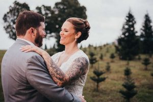A Connecticut bride and groom stand in the middle of a Christmas tree farm