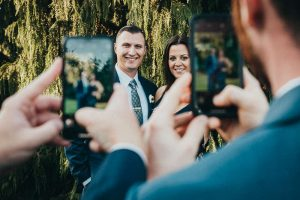 Guests at a Rhode Island wedding take photos of a groomsman and his date