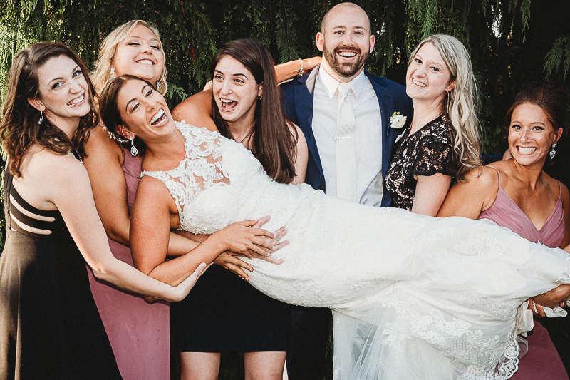 A Newport, Rhode Island bride is help up by her groom and friends during cocktail hour. By choosing a wedding photographer that matched their personalities, this couple ensured a good time on their wedding day.