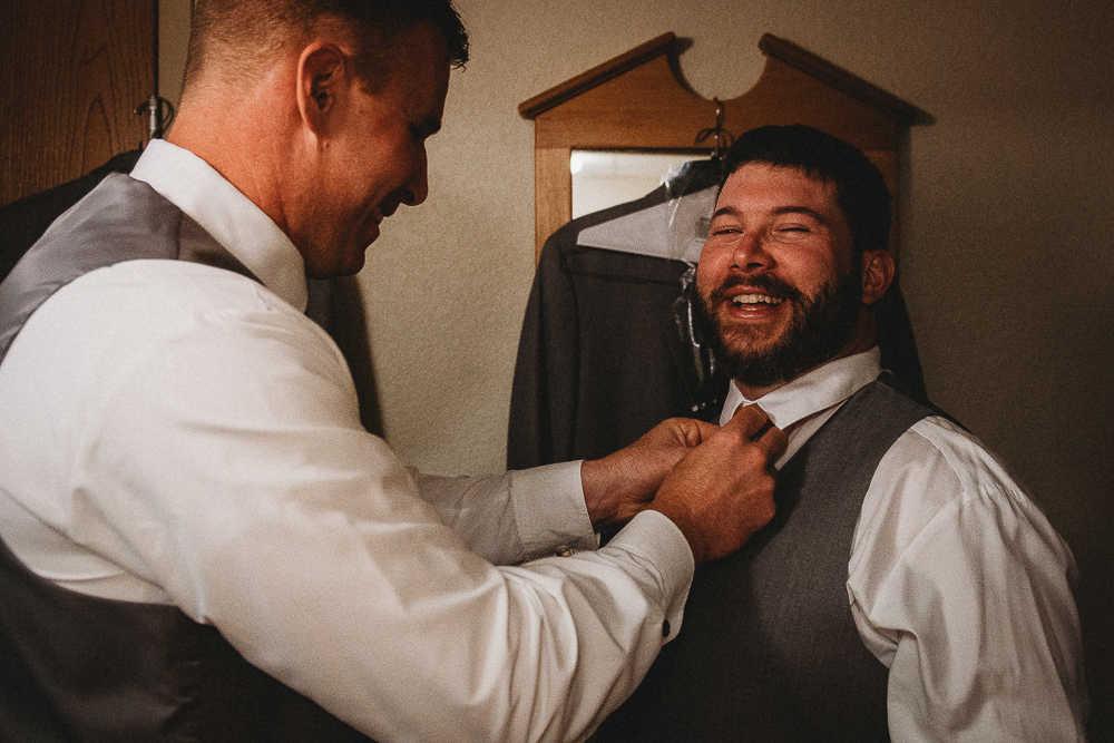 A groomsmen helping his groom friend