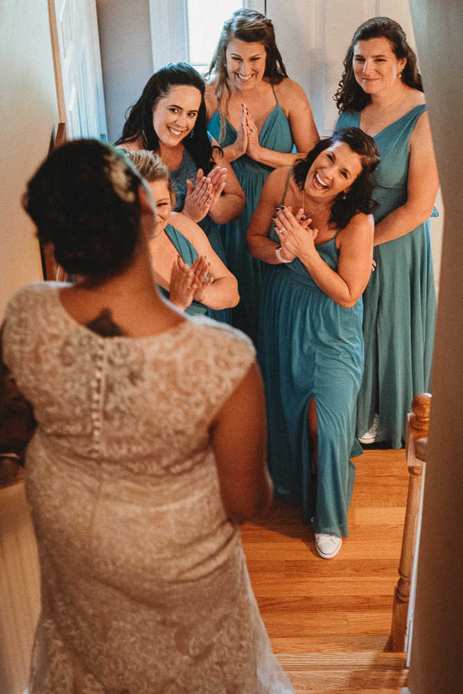 Bridesmaids greeting the bride on a staircase before her The Overlook at Geer Tree Farm wedding