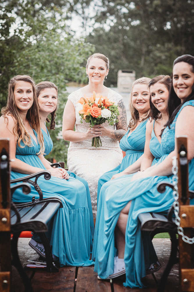 A smiling Conneticut bride on a tractor with her bridesmaids