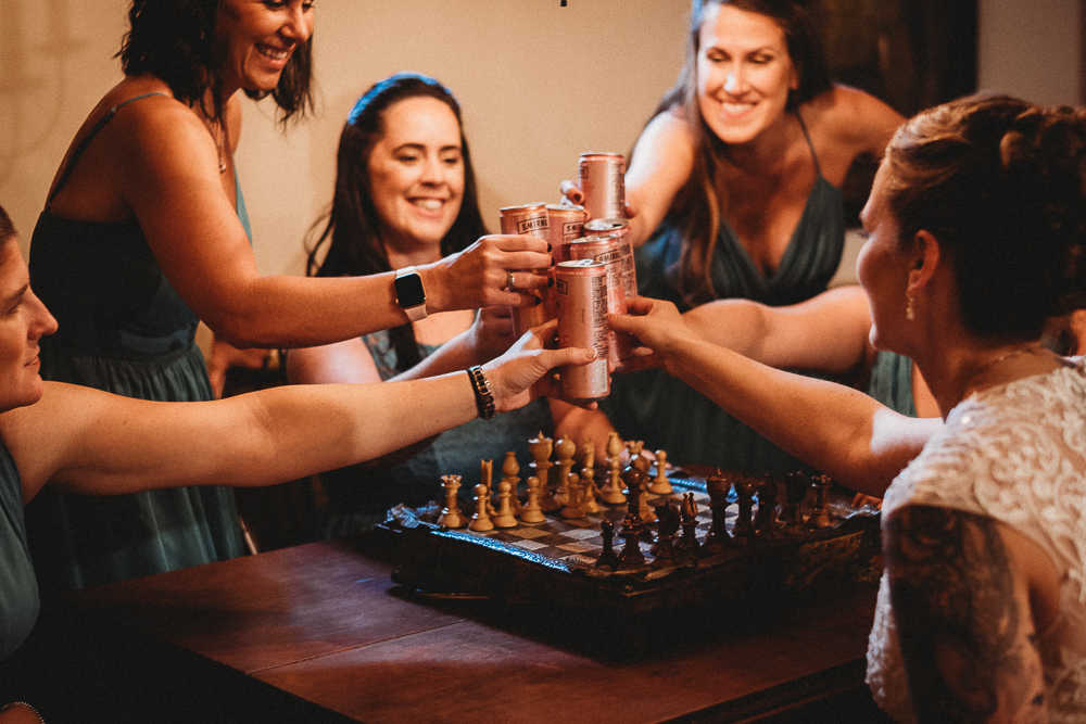Bridesmaids playing chess and enjoying drinks before a Connecticut wedding