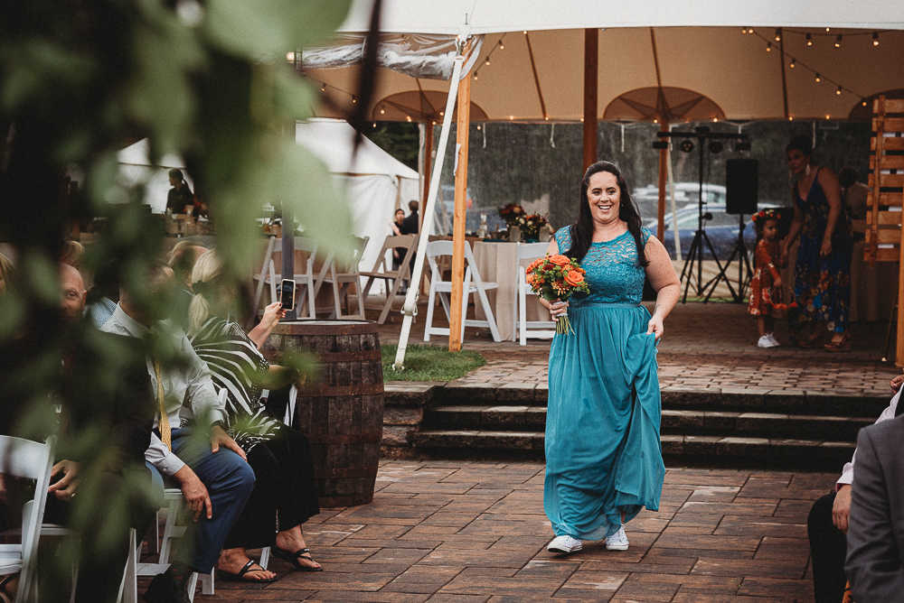 The maid of honor walks down the aisle in her blue dress