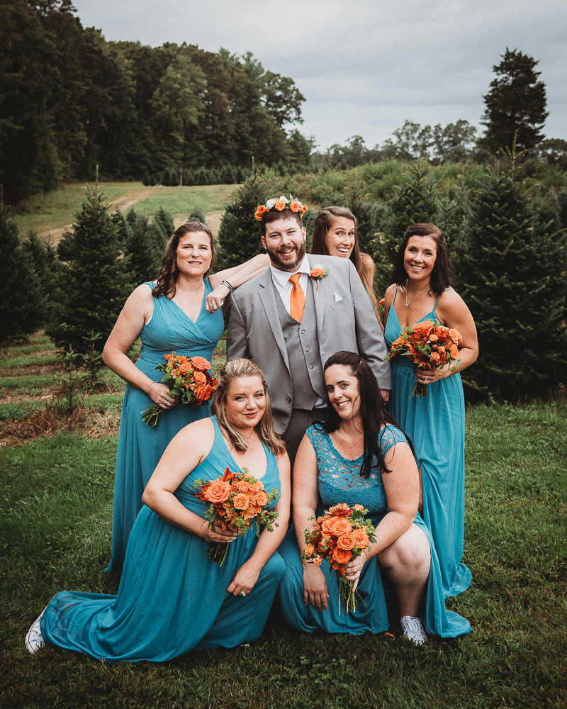 The groom hanging out with the bridesmaids after his The Overlook at Geer Tree Farm wedding ceremony