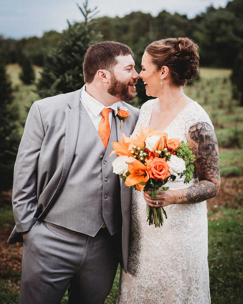 The bride and groom touching noses at a Connecticut tree farm wedding