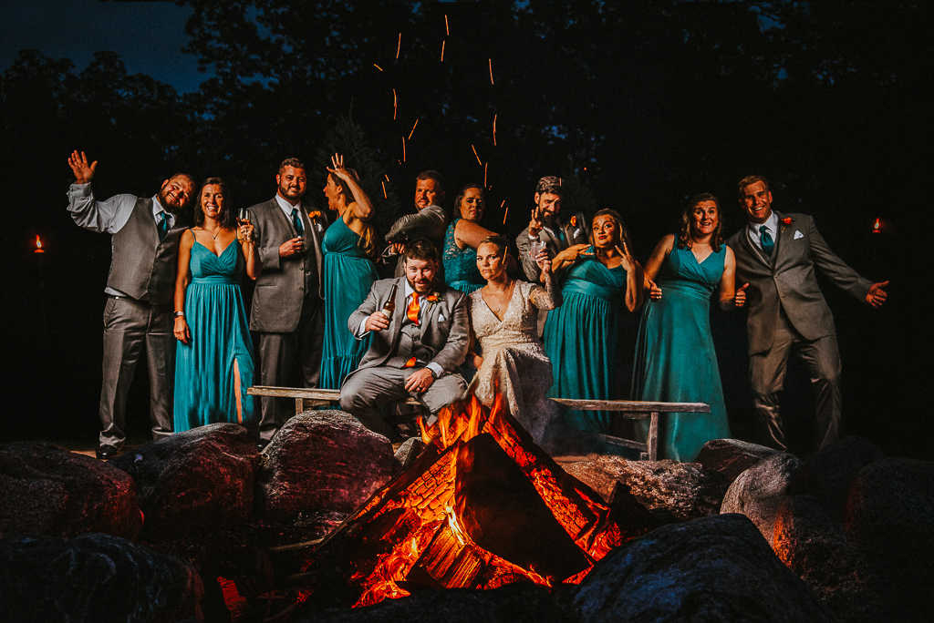 Wedding party, bride, and groom enjoying a fire at The Overlook at Geer Tree Farm