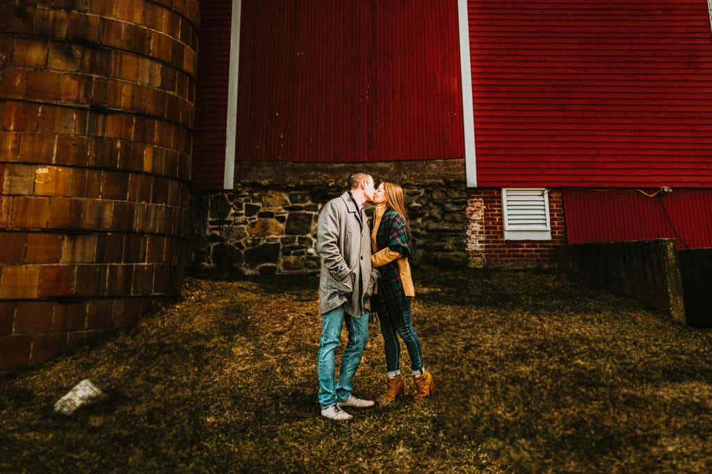 A couple poses in front of a large, red barn at the University of Connecticut during winter.
