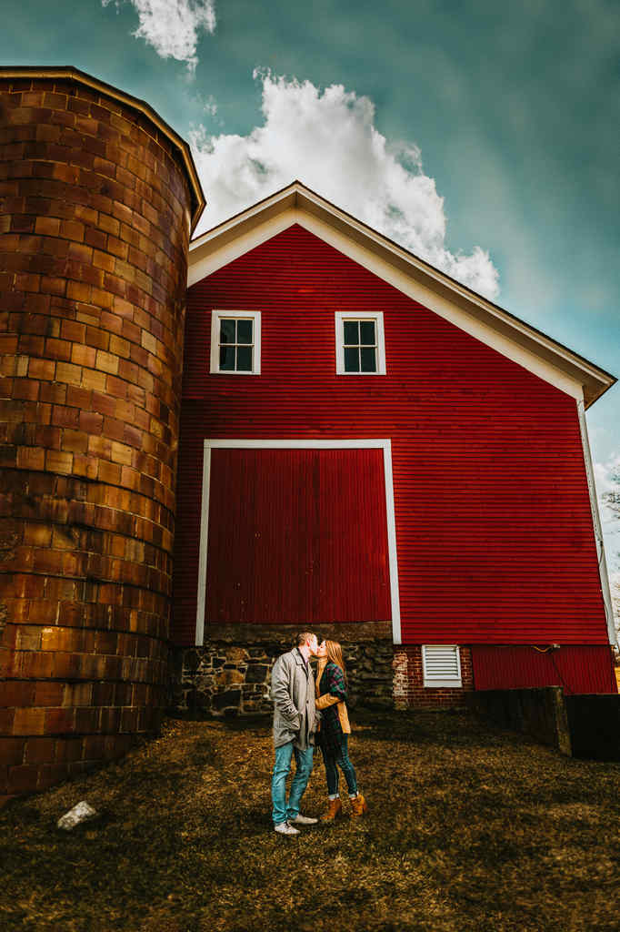 An engaged man and woman kiss in front of a large, red barn on the University of Connecticut campus during an engagement photography session.
