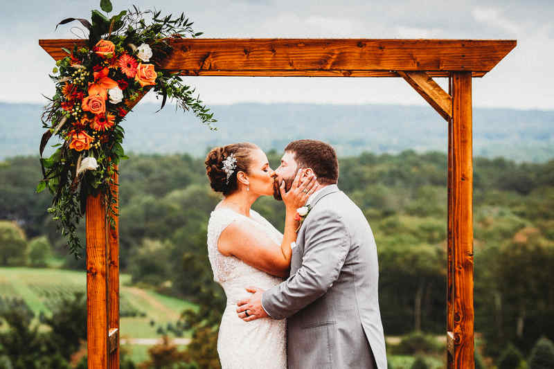 The bride and groom have their first kiss at The Overlook in Griswold, Connecticut