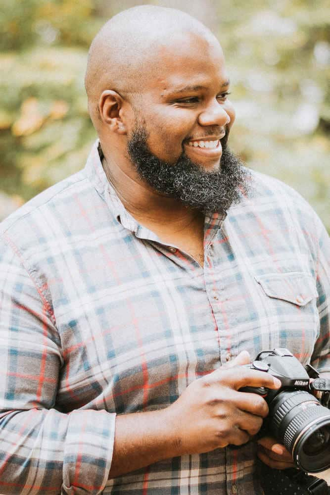 Connecticut wedding photographer Terrence Irving poses with a Nikon camera.
