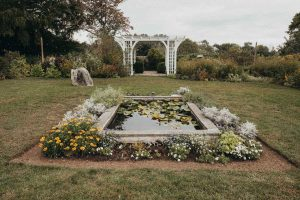 A white pergola sits in the background and a rectangular concrete pond in the foreground of the Stone Acres Farm wedding ceremony area.