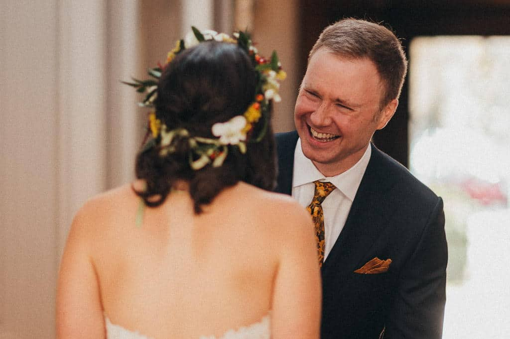 A happy groom smiles at his bride during a first look after successful implementation of wedding planning tips guided them to their wedding day.