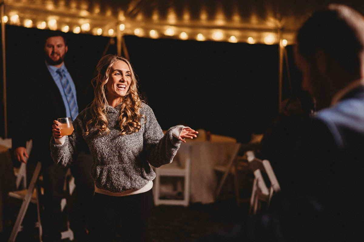 A Connecticut farm wedding bridesmaid dances with a drink in her hand with string lights lining the inside of the tent.