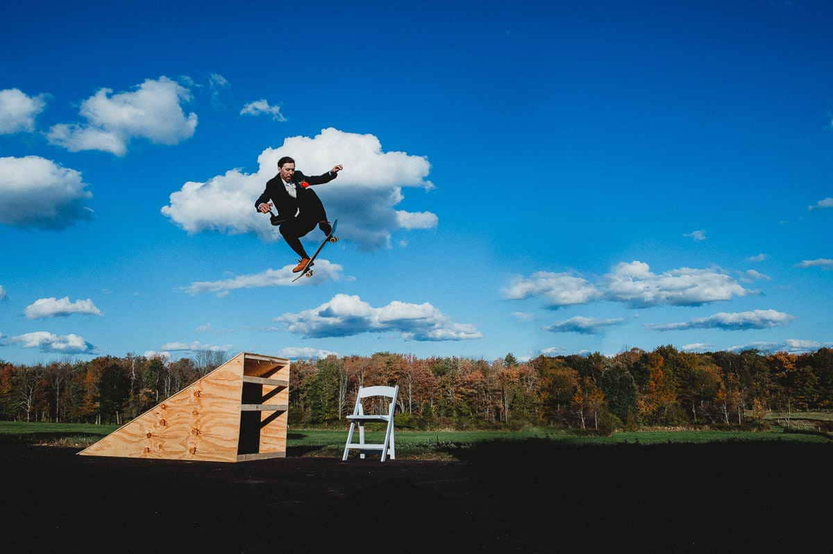 A skateboarding Connecticut farm wedding groom practices jumping over his bride by launching himself off a ramp over a chair.