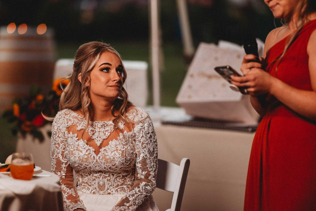 A sitting bride is on the verge of tears as her maid of honor reads a speech from her phone. A prime wedding planning tip is that the little moments stick with you for a lifetime.