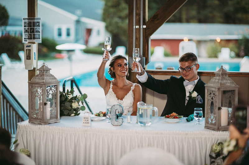 A bride and groom raise their champagne glasses at budget Connecticut wedding venue Boulder Ridge Day Camp.
