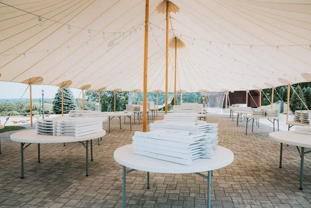 A view underneath the reception tent as preparations are being made for a The Overlook at Geer Tree Farm wedding.