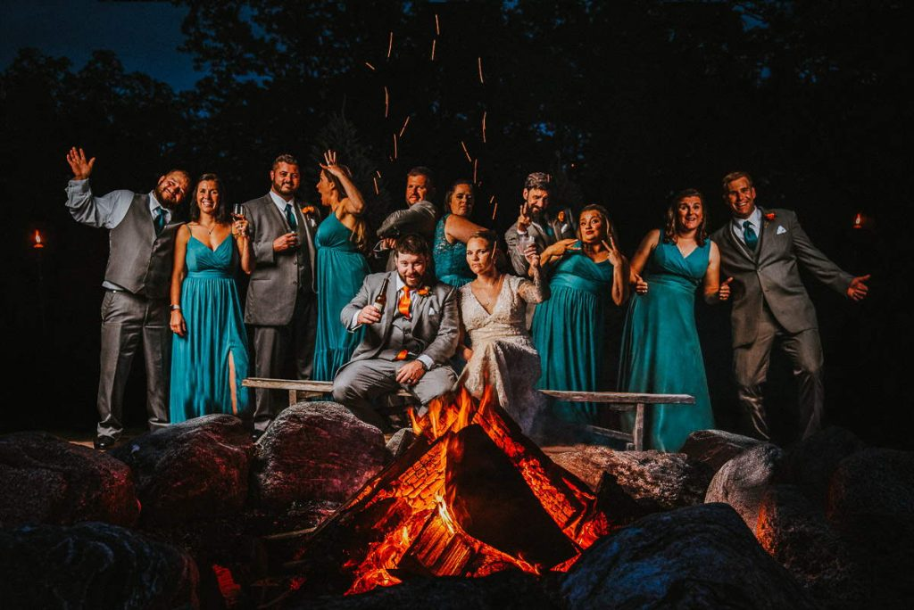 A bride and groom sit front and center behind a fire pit as the rest of their wedding party smiles around them during their The Overlook at Geer Tree Farm wedding.