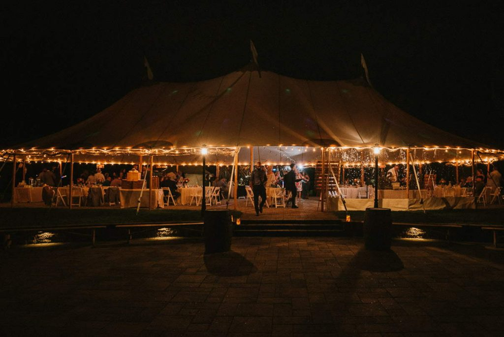 The reception tent of The Overlook at Geer Tree farm at night during a summer wedding.