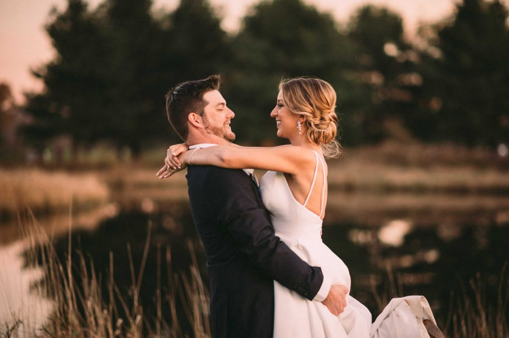 Image from Connecticut wedding venue Lyman Orchards, with a groom lifting his bride off the ground as the two smile at each other under a sunset.