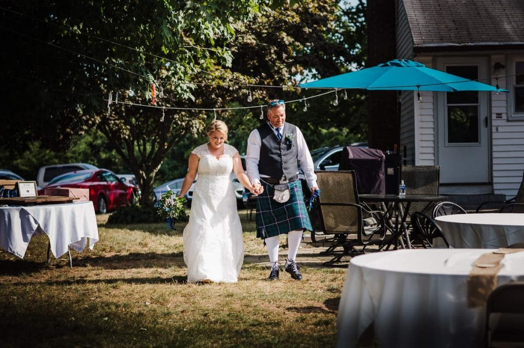 A bride and groom enter the reception of their backyard wedding, walking hand in hand. Their house and the guests' vehicles are in the background and a table in the foreground.