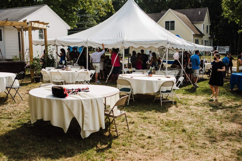 A tent, tables, and guests outdoors at a Connecticut backyard wedding.