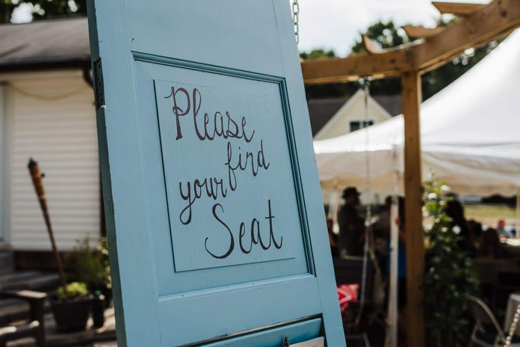 """A blue window shutter repurposed as a sign reads """"Please find your seat."""" Custom and/or DIY signage is a great option when planning a backyard wedding."""