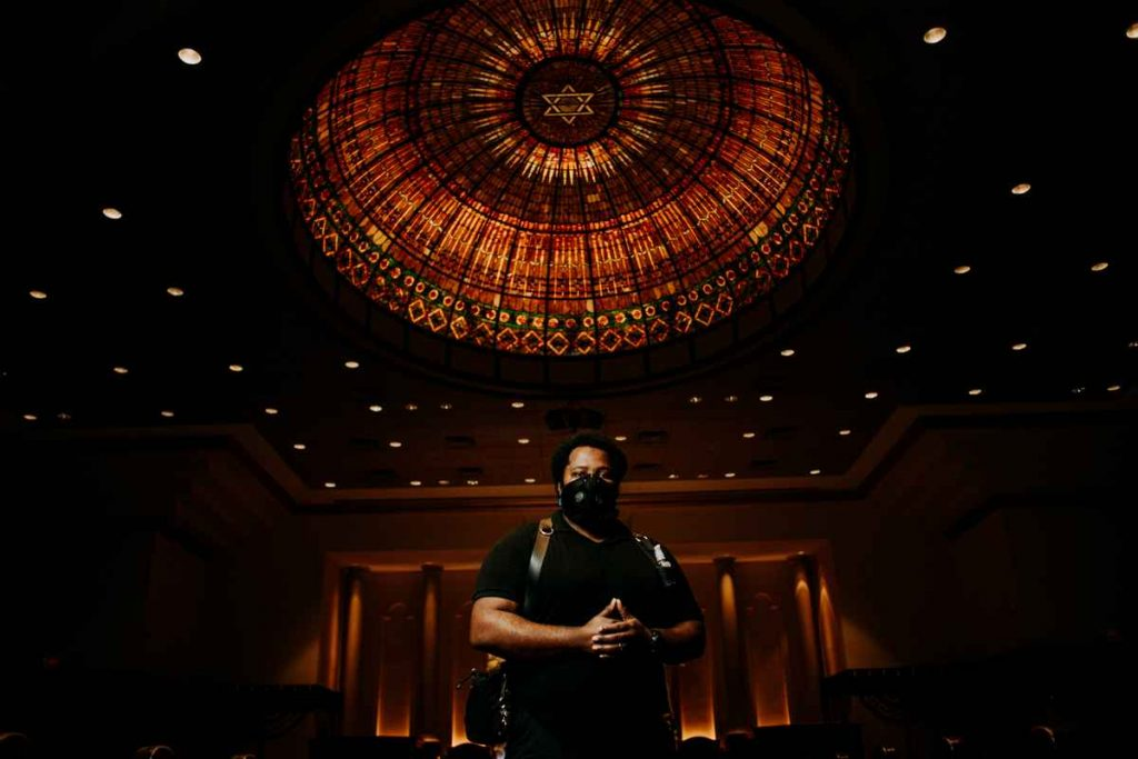 Connecticut wedding photographer Terrence Irving poses underneath a Star of David in a synagogue during a wedding break while wearing a mask.