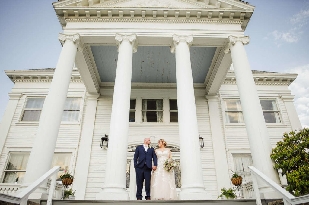 A bride and groom stand on the exterior landing of Haley Mansion during their Mystic, CT wedding at Inn at Mystic.